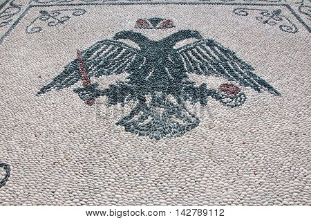 Pebble stone floor with a picture of double eagle Rhodes.