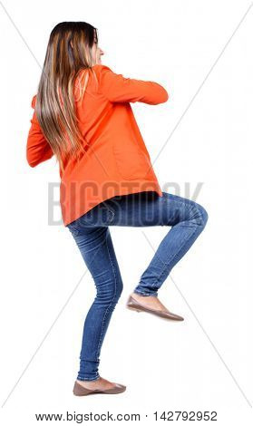 back view of woman funny fights waving his arms and legs. Rear view people collection. backside view of person.  Isolated over white background. business woman in a red jacket kicks.
