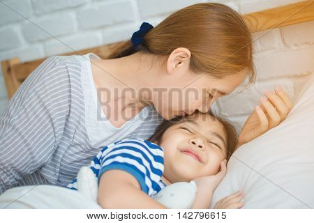 Asian mother awaking her daughter on the bed in the morning