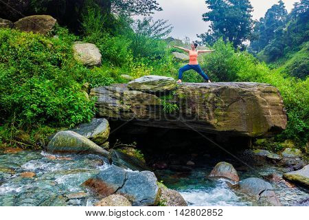 Yoga outdoors - sporty fit woman doing Ashtanga Vinyasa Yoga asana Virabhadrasana 2 Warrior pose posture at tropical waterfall