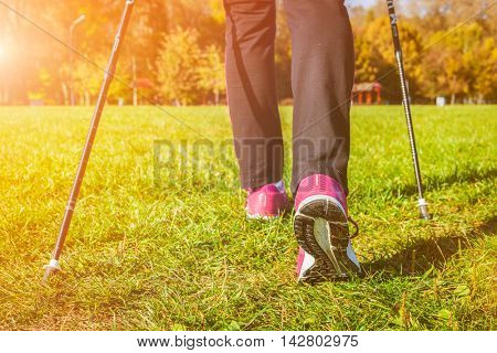 Nordic walking adventure and exercising concept - woman hiking, legs and nordic walking poles in summer nature. With lens flare and light leak.