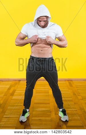 Young Bodybuilder Flexing Muscles On Yellow Background