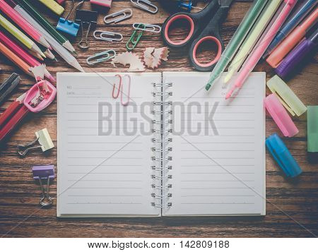 Top view notebook and office suplies on wood table made vintage-retro style
