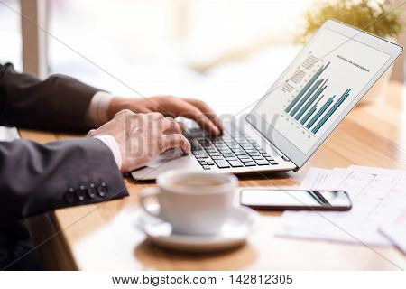 Much work to cope with. Close up of laptop standing on the table while pleasant man using it while working in the office