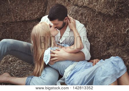 Man kissing a woman in the hayloft they are lovers.