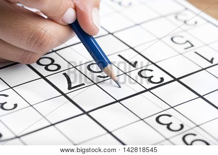 Woman hand holding a pencil and solving sudoku, popular puzzle game with numbers.