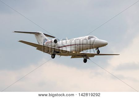 Kiev Ukraine - July 31 2012: Cessna 525A CitationJet CJ2 business jet is landing with cloudy sky on the background