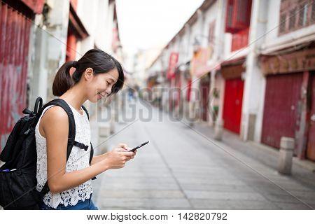 Woman sending sms on cellphone in Rua da felicidade