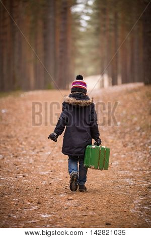 A small cute boy in the hat with pompom and warm jacket walking in the nice forest and carrying a bright green suitcase. Young traveler ready for adventures.