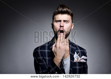 Portrait of young man wriggles in studio over gray background. Hypster gay covers open mouth with his hand. grimanced, fright, fear, surprised, grotesque.