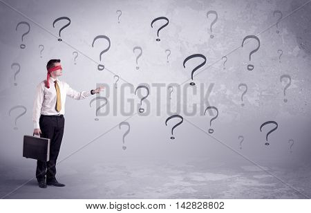 An amateur young sales person lost in a new situation concept with blindfolded businessman surrounded by drawn question marks.