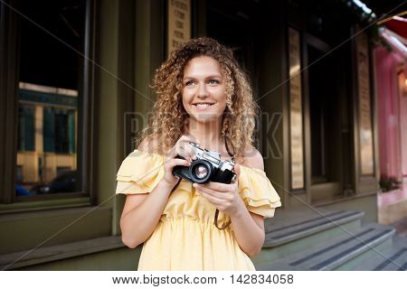 Young beautiful photographer in yellow dress smiling, walking around city.