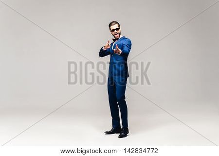 Choosing you. Full length studio shot of handsome young smiling man in full suit and bow tie looking at camera and gesturing