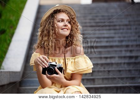 Young beautiful photographer in yellow dress and hat smiling, walking around city.