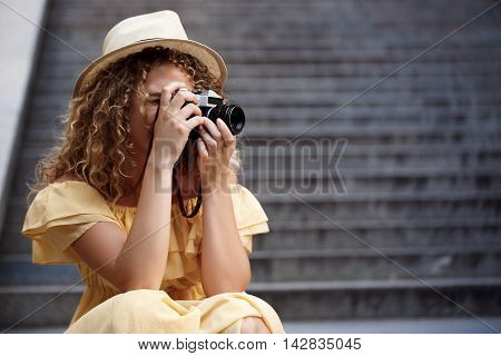 Young beautiful photographer in yellow dress and hat walking around city.