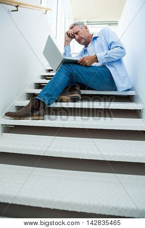 Full length of tensed mature man using laptop on steps at home