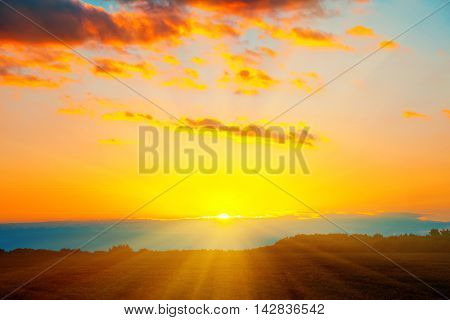 Beautiful Blazing Sunset Landscape At Over The Meadow And Orange Sky Above It. Amazing Summer Sunris