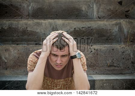 Photo of the Young depressed man with hand on forehead. Crisis stress concept. Human emotion facial expression