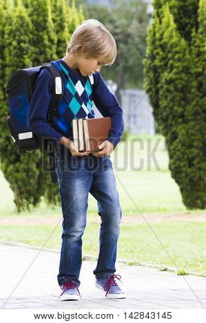 Serious child with backpack carring books in his hands. Outdoor. Education back to school people concept.