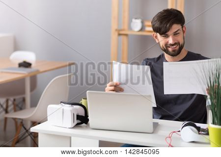 Addicted to work. Positive content man sitting at the table and working with papers in the office while expressing joy