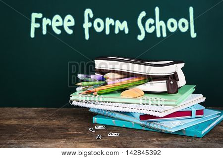 Home learning concept. Pencil case with various stationery on table, on blackboard background