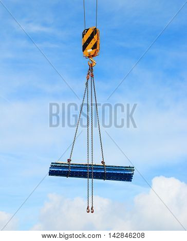 Yellow crane hook lifting load over clouds on blue sky. Construction industry background.
