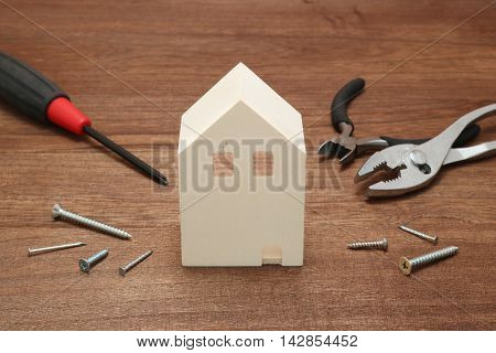 Miniature house and tools in front of brick wall. Concept of repair house. Repair and construction of the house.