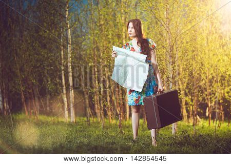 Young lost woman with a suitcase and a map in woods; lens flare