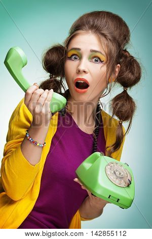 Surprised young pretty woman talking on telephone