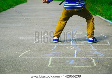 little boy playing hopscotch on playground outdoors, kids activities