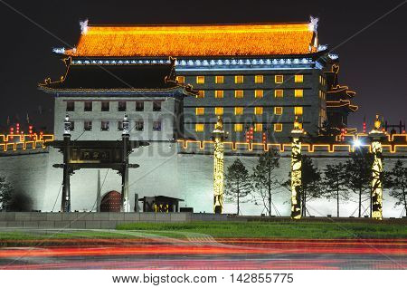 The south gate or (Yongning men) and archery tower at the Xian city wall lit up at night in Shaanxi province China.
