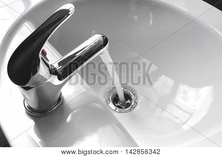 Water tap faucet with flowing water in a white bathroom sink.