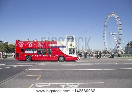 Site Seeing Bus Drives Over Westminster Bridge With London Eye In Background