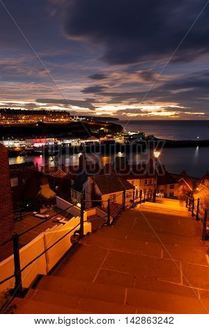 WHITBY ENGLAND - AUGUST 12: Whitby town and the famous '199 steps' in the evening against a dramatic sunset. In Whitby North Yorkshire England. On 12th August 2016