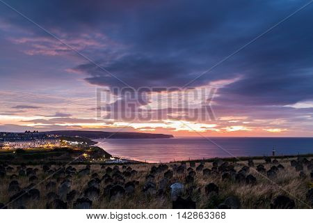 WHITBY ENGLAND - AUGUST 12: Whitby St Mary's church graveyard against a dramatic sunset. In Whitby North Yorkshire England. On 12th August 2016