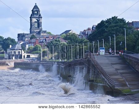 SEACOMBE, ENGLAND, JUNE 29. The Seacombe Promenade on June 29, 2016, in Seacombe, England. Waves crash along the Seacombe Promenade in Seacombe England as the Wallasey Town Hall looms in the background.