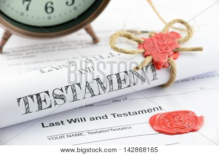 Rolled up scroll of last will and testament fastened with natural brown jute twine hemp rope sealed with sealing wax and stamped with alphabet letter B. Decorated with an antique clock on a table.