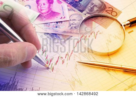 Hand holding a blue ballpoint pen is analysing a technical chart of financial instrument. A concept of forex / currency trading trend analysis for investor who want to maximize portfolio profits.
