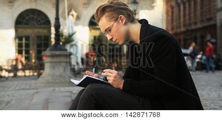 young student preparing for the exam in old center of europe city Lviv (education knowledge self-development self-improvement)