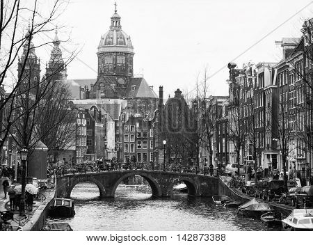 The Oudezijdsvoorburgwal  a street and canal in the Red-light district  in the center of Amsterdam. In the background The Basilica of St. Nicholas.  Black and white