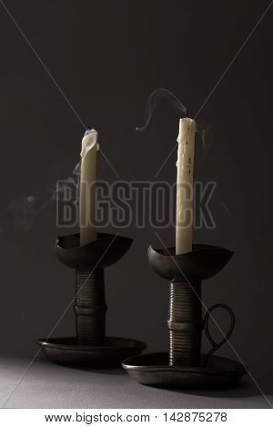 Two Blown Out Smoking Candles on Iron Candlesticks