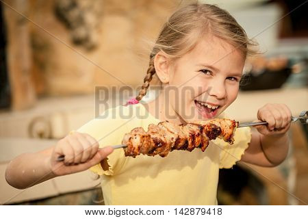 Little beautiful smiling girl with pleasure eats shish kebab outdoor at the day time. Concept of healthy life.