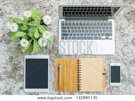 Closeup brown note book brown pen computer notebook tablet phone and artificial plant with white flower on gray fabric capet textured background in top view