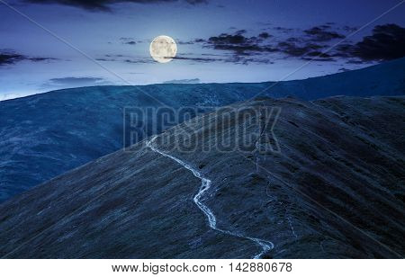 winding road through large meadows on the hillside of Polonina mountain range at night in full moon light