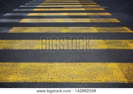 Yellow pedestrian crossing with white stripes on tarmac. Crosswalk on asphalt road. Safety marking.