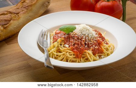Spaghetti with marinara in a white bowl on a wood surface
