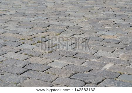Geometry pattern of cobblestone pavement cladding with moss between stones