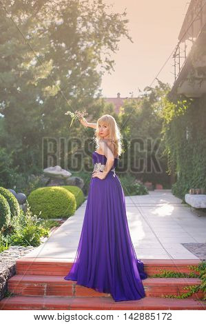 Portrait of beautiful woman dressed in evening gown. Blonde gorgeous woman in long purple luxurious dress posing in garden. Woman holding bouquet of wildflowers.