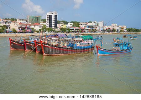 NHA TRANG, VIETNAM - DECEMBER 30, 2015: Fishing schooners in the background of the city's waterfront on the river Kai. Asia, Vietnam