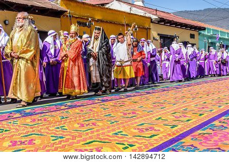 Antigua Guatemala - March 25 2016: Locals reenact biblical scenes walking over handmade dyed sawdust carpets on Good Friday in colonial town with most famous Holy Week celebrations in Latin America.